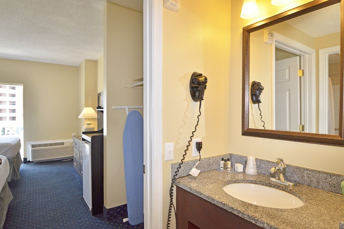 bathroom with hair dryer, iron, and ironing board