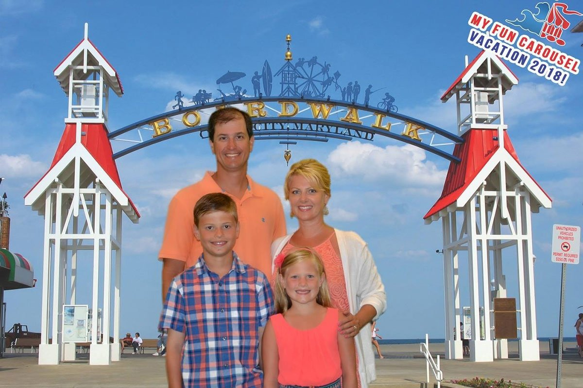 smiling family posing in front of Boardwalk entrance sign