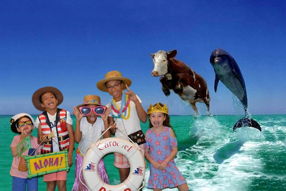 children in whimsical beach attire posing in front of cow and dolphin leaping out of water
