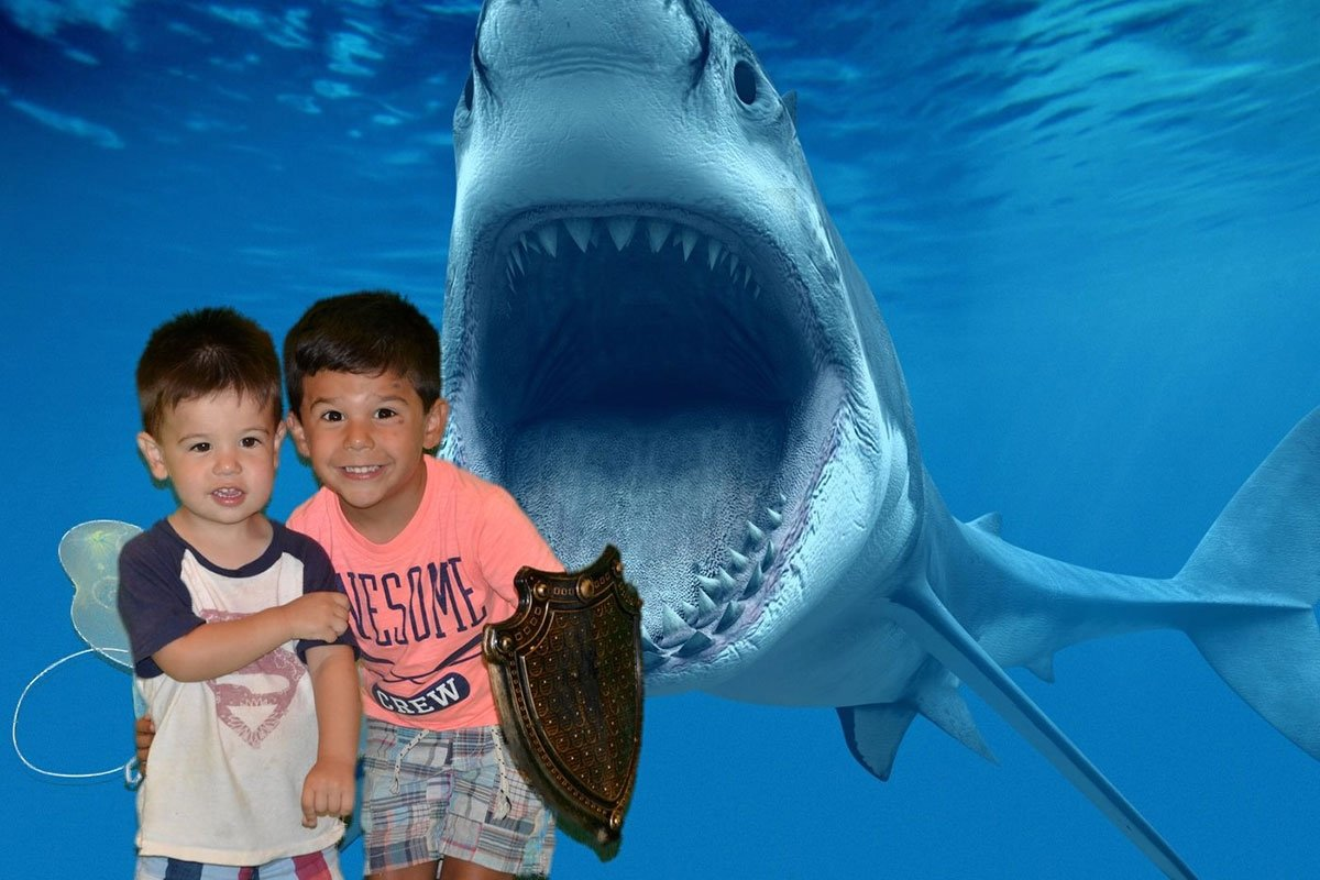 two young boys pose in front of shark with jaws open