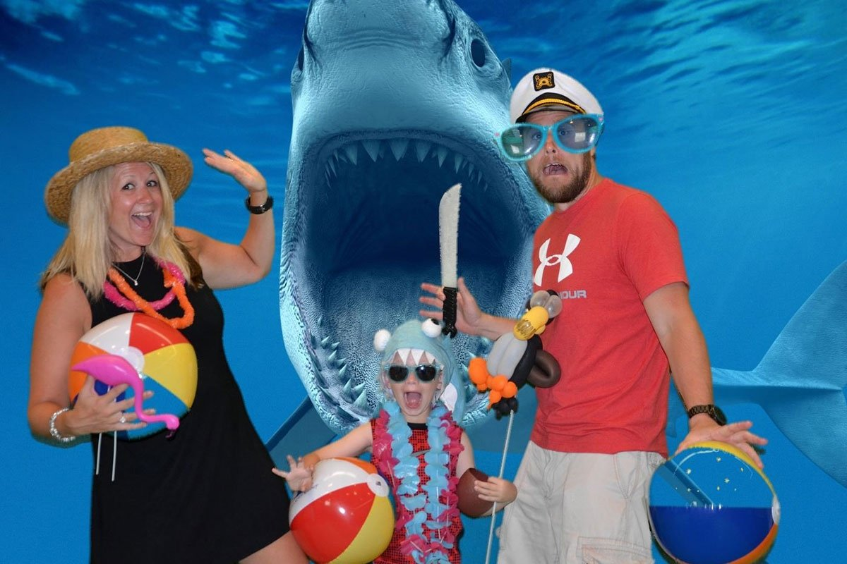family in whimsical attire pose in front of shark with jaws open