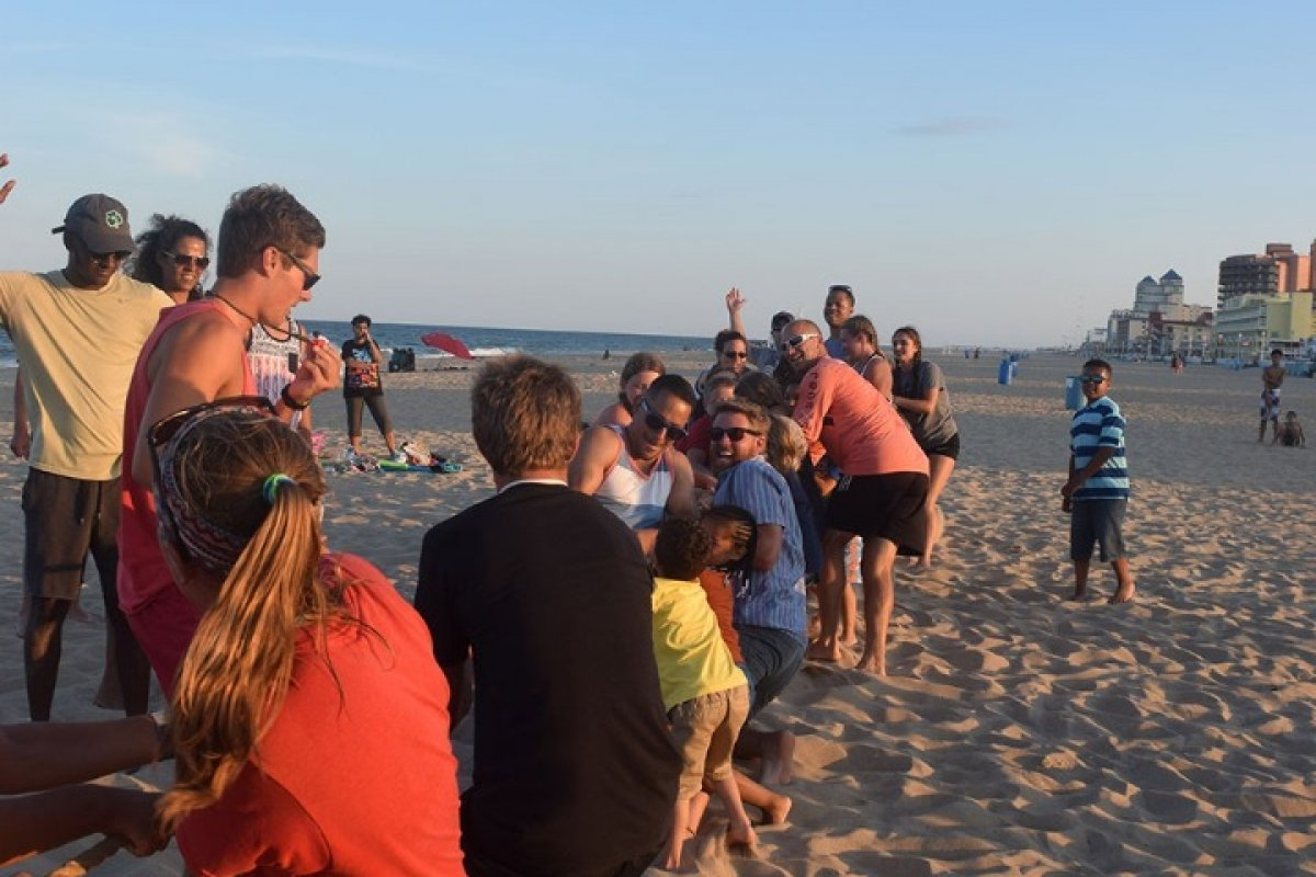 adults and kids playing tug of war on beach